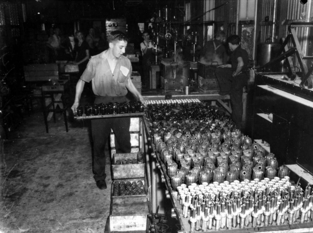 A factory worker stacking crates of hand grenades, Brisbane, ca. 1942