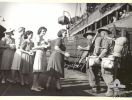 Townsville, Qld. 1945-03-25. Australian Comfort Fund workers greeting soldiers from the H.T. Katoomba with bags of fruit