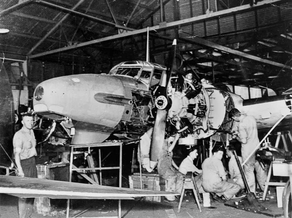 Airforce mechanics working on the engine of a Avro Anson aircraft