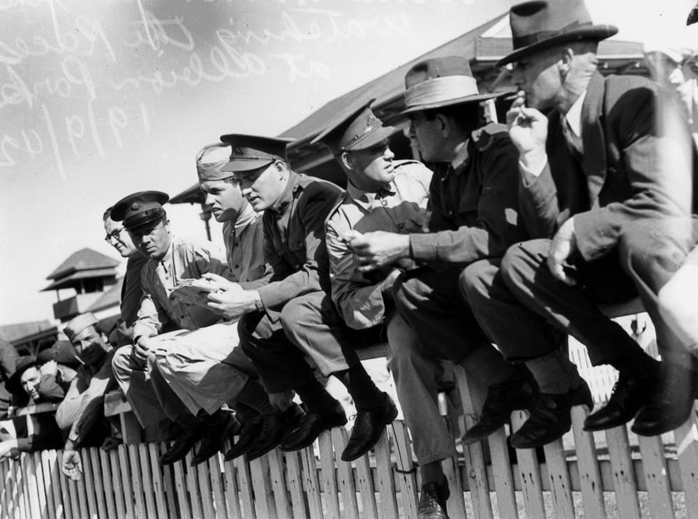 Soldiers sitting on the fence watching the races at Albion Park, Brisbane, September 1942